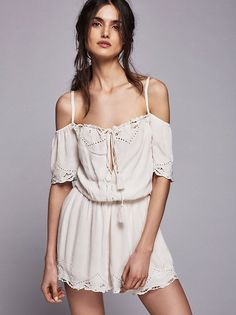 White Romance Romper   Off-the-shoulder romper featuring eyelet embroidered detail and keyhole cutout at the bust with drawstring tie. Elastic waistband and neckline with adjustable ties at the back for an easy, effortless fit. Sweet scalloped trims add a femme effect. Lined.