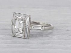 Antique Art Deco engagement ring made in platinum and centered with an EGL certified approximately 1.40 carat emerald cut diamond with…
