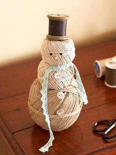 Snowmen made with three stacks of yarn, spool for hat, buttons, and staight pins. Too cute! Gonna make!