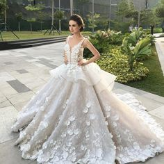 Ballgown style wedding dress with intricate petal designs etched onto skirt // Filipino designer Mak Tumang studied interior design before delving into fashion in the Philippines. His love of opulent costumes and architecture influences his designs and this can be seen in his gowns which are rich in elaborate detail.