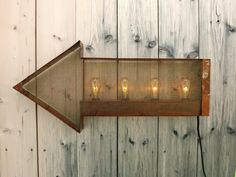 "Rusty arrow sign wall light. This arrow is 25"" long and 12"" tall. It features 4 edison bulbs behind a brass screen, and a rusty patina coated in lacquer. The sign plugs into any household outlet with it's 6' black cord sporting a flick switch. The bulbs are 7w clear edison style with spares avaliable from my shop."