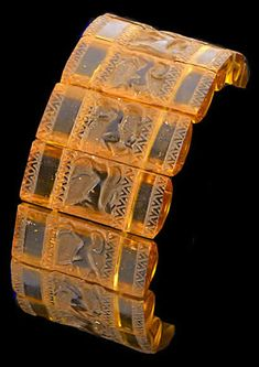 """Lalique 1928 'Griffons' Bracelet: amber glass in 14 pieces on elastic bands, each glass part is 1.24"""" long by .5"""" wide"""