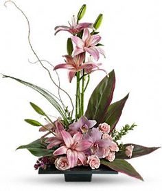 pink asiatic lilies, pink roses and pink cymbidium orchids are presented with variegated ti leaves, bear grass and curly willow.