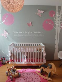 Pink & grey girl's nursery design with grey walls paint color, white modern cot, red & pink doily rugs, white & pink wall stickers, string light pendant and pink butterflies. LOVE!