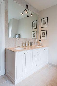 Baderomsinnredning med marmor benkeplate og underlimte vasker. Stort innfelt speil