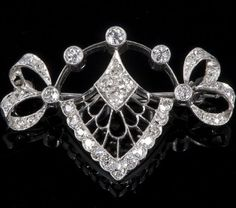1920s white metal and diamond bar brooch of Belle Epoque design with old cut diamonds set to ribbon terminals, five graduated old cut diamonds in millegrain settings arranged in an arch above a diamond set openwork panel below (measuring 33mm).