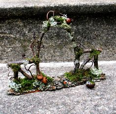 A twig portal into an enchanted world--perfect for a miniature garden or a focus for faery meditation. Horse chestnut twigs form an arch and two side fence segments adorned with moss, lichen, acorns, curly grapevine tendrils and a tiny snail shell. Fairy Garden Furniture, Fairy Garden Houses, Fairy Village, Fairy Garden Accessories, Fairy Doors, Miniature Fairy Gardens, Miniature Dollhouse, Fairy Land, Garden Gates