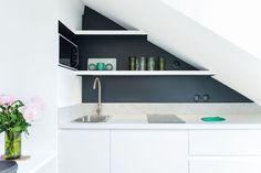 La cuisine sous les toits dans un studio de 18 m2 sobre et élégant, rénové par Stephan Bidoux.