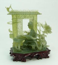 """A nicely carved Chinese translucent green serpentine jade sculpture depicting a meiren playing a zheng. Behind her is wall with moving reticulated windows. Surrounded by foliage and flying birds. Includes fitted wooden base. Circa 19th/20th century. 7 1/4"""" height x 6"""" width (18.4cm x 15.2cm). Jade weight of 528 grams."""