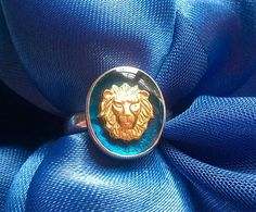 A fabulous lion with incredible detail, down to his tiny whiskers...Stunning vibrant translucent blue enamel. The ring is sterling silver and the Lion is gold and preserved in a technique I have devised that means that the gold will never fade or tarnish. The ring is a size M, US size 6 and a half, but I can make other sizes, just contact me. The front of the ring is just over half an inch tall...check out my other miniature portrait pieces too.