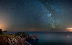 The Milky Way fills the night sky over the Durdle Door rock archway on the Jurassic Coast in Dorset, England. The picture was taken by Andrew Whyte, who has a passion for long exposure photography and experimenting with night time shots.
