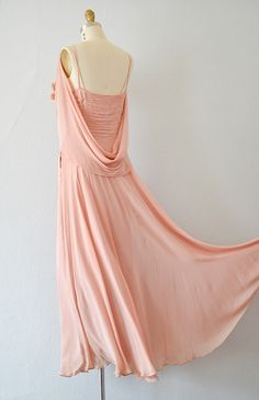 1930S ROMANTIC PINK DRAPED GOWN. The romantic rose pink gown has gathered bodice with sweetheart neckline decked with clusters of pink blossoms. The thin double straps can be worn elegantly off the shoulder and the attached cape drapes with subtle drama. Back