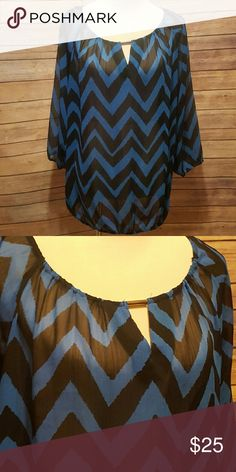 Blue chevron blouse Quarter length sleeves. Silver piece at rounded neckline. Blue and black chevron. Banded waist. Sheer.  Looks great with a black cami underneath and jeans Tops
