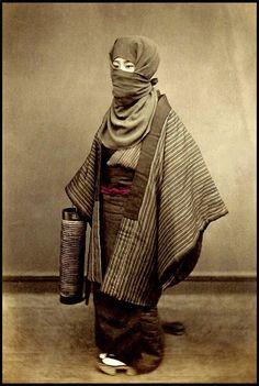 明治時代初期に撮影されたとされる写真。 御高祖頭巾を身につけた冬の装い。方形の布に耳をかける輪をつけており、耳にかけて顔を出す被り方と、目の周りだけ出す被り方がある。
