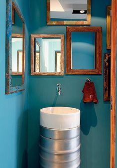 Nas paredes do lavabo, a cor turquesa contrasta com as molduras de madeira de demolição. Projeto da arquiteta Luciana Penna