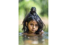 マヌー国立公園の奥深く、ヨミバト川で水浴びをするマチゲンガ族のヨイナ・マメリア・ノンツォテガ。頭の上に、ペットのセマダラタマリンを乗せている。 Photographs by Charlie Hamilton James