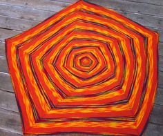Free Knitting Pattern for Spiral Light Baby Blanket - Pentagonal baby blanket knit in the round with increasingly wider bands of 3 colors create an illusion of spiraling pentagons. Perfect for 2 multi-color skeins with colors in the same color family with a complementary semi-solid. Designed by Lorla Luden.