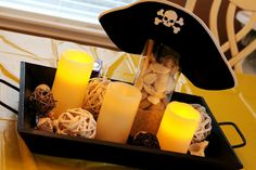 Table Decor with pirate hat, candles, sand, shells, twine, etc... for a Pirate birthday party