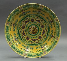 """Chinese famille jaune large porcelain shallow dish, late Qing/early Republic period, the well centered with a shou medallion framed by five aubergine bats alternating with lotus accented with green tendrils on a yellow ground, the interior decorated with the Eight Buddhist Treasures and an everted rim with confronting phoenix, the exterior with bats and peach sprigs, the recessed base with an apocryphal Yongzheng mark, 13.75""""w"""