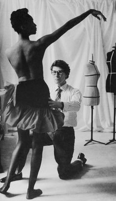 Yves Saint Laurent fitting a model.  He was the first designer to use black models in his runway shows, propelling the career of Mounia a Martinique-born beauty