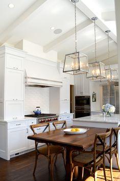 White kitchen with hanging lantern lights, dark hardwood floors