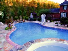This custom designed, swimming pool is lagoon shaped, and has a travertine coping with Crab Orchard flagstone for the patio.  The landscape softens the look.  There is a waterfall on one end, a slide and hot tub with water spilling into the pool on the opposite end.  A beautiful pool.  Minks Landscape & Pools. London, KY