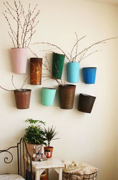 love this little plant wall display using a tins painted in a variety of bright, fun colors ~ photo from by Rubyellen of Cakies blog featured on A Beautiful Mess blog