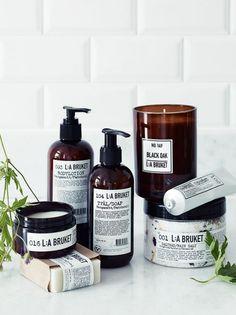 skin care line, dark bottle packaging, foliage, white subway tiles, product shoot