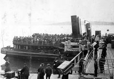Two crowded tenders (the Ireland & America) - loaded with passengers waiting to be ferried to the Titanic, anchored at Cork Harbor, Queenstown (Cobh), Ireland.  This was the Titanic's last port of call before sinking into the Atlantic 3 days later - 100 years ago.