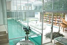 glass swimming pool sits in the middle of this contemporary home located in Hampstead Village, London, UK