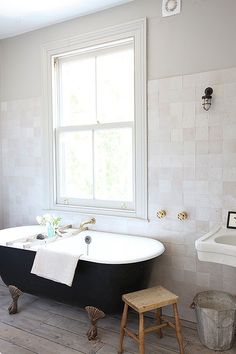 We love the neutral tones running through the bathroom tiles and wood flooring. The black bath stands out all the more as a statement piece in the space.