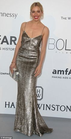 Sparkler: Sienna Miller cut a dreamy figure as she graced the red carpet at the amfAR Gala on Thursday, her slender figure covered in a slinky metallic gown that looked perfected with her scarlet red lip and blonde hair pulled back into a chic up-do