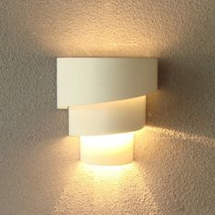The Loopy wall sconce captures the thrills and chills of a roller coaster ride as its spiraling, offset, three-tiered metal shade stacks up for a stunning, all-white effect. It is an artfully abstract