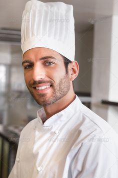 Happy young chef smiling at camera in a commercial kitchen ... 20s, Chefs Hat, Commercial Kitchen, Looking At Camera, attractive, catering building, cheerful, chef, chefs whites, confidence, confident, handsome, happy, head chef, hispanic, hotel, indoors, job, kitchen, male, man, occupation, portrait, profession, professional, restaurant, smiling, standing, uniform, young adult