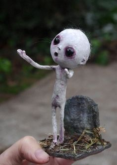 Paper mache and paper clay doll with diorama. Hand made and painted. No molds used.  Is about 12 cm (4,72 inches) high and the base is about 6 cm (2.36 inches) square  The diorama is decorated with sand and straw