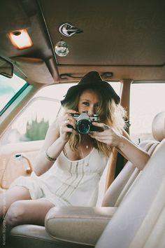 Pretty stylish girl playing with camera inside of old car by Kristin Rogers Photography. An exclusive image for Stocksy.com
