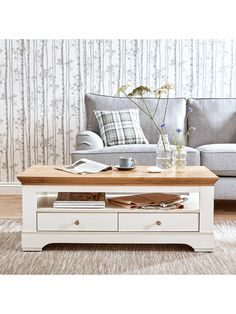 Ideal HomeWiltshire 2 Drawer Coffee Table in Cream. This Wiltshire storage coffee table from Ideal Homeis traditionally designed with a chunky style, shaped plinth and top, and dainty metal handles. Its soft cream colour helps highlight the rustic oak-effect top, which has been thoughtfully detailed with intricate grain patterns and fine cracks for added character - just like you'd expect to find on the real thing.