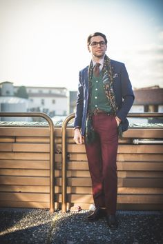 A navy blazer over a green cardigan, paired with burgundy pants, a brown necktie, and a patterned scarf. Great menswear style!