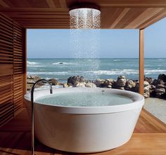 Geo 180 free-standing tub by Zucchetti Kos with Rain shower overhead.