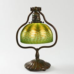 """This is not contemporary - image from a gallery of vintage and/or antique objects. Tiffany Harp Desk Lamp Tiffany Studios table lamp with a blown green iridescent Damascene glass shade in a patinated bronze """"harp"""" base with ribbed foot."""