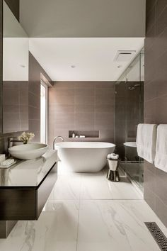 Bathroom Tile Ideas - Use Large Tiles On The Floor And Walls // The large tiles featured on the walls of this bathroom bring out the darker flecks found in the tiles used for the floors.
