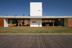 Gallery of Joanopolis House / UNA Arquitetos / 1:100 / Horizontal HOuse / 1 level / finish condition / half buried house / sloping terrain / open space / 2 free facades house / patio house / water tank element / wood blind sliding brise soleil / front facade view house / green terrace house /
