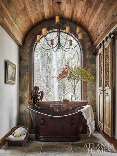 Wood and stone elements, along with a copper tub, blur the lines between inside and out in the master bathroom. Copper Tub, Copper Bathroom, Stone Bathroom, Clawfoot Tub Bathroom, Rustic Master Bathroom, Atlanta Homes, Stone Houses, Winter House, Log Homes
