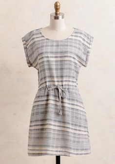 Darling and casual, this day dress features a striped pattern in hues of cream and blue. Designed with pockets at the side and cuffed cap sleeves, it's finished with a self-tie bow at the waist f...