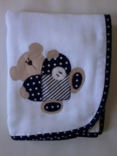 Confeccionada em tecido fralda com 04 camadas para melhor absorção. Patch apliquée e viés em tecido 100% algodão. <br>*As cores para o viés e o tema para o aplique podem ser escolhidos. Consulte disponibilidade. <br>**Ideal para secar bebês recém-nascidos.