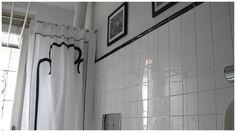 Tenda da bagno in piqué con disegno che riprende quello del corridoio antistante e con finitura interna in plastica.