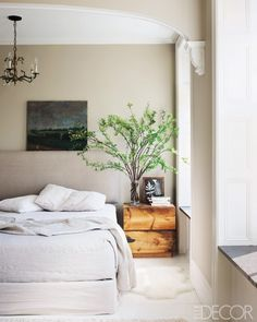 Elle Decor Bedroom, love the minimalist feel with the colors, the chandelier and the plant--makes the space feel light