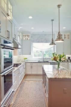 It's no chore dreaming up meals in this gorgeous kitchen. White walls and cabinets make the mood fresh and airy while stunning marble countertops and graphic patterned rugs bring a note of luxury.
