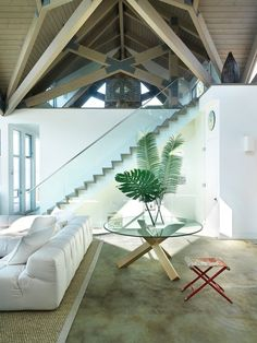 The glass staircase enhances the airness of the living area and infuses the design with a Zen-like calm.