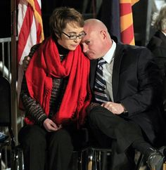 Mark Kelly leans on the shoulder of his wife, U.S. Rep. Gabrielle Giffords, at a memorial vigil remembering the victims and survivors of the shooting that wounded Giffords, 12 others and killed six (AP Photo/Ross D. Franklin)